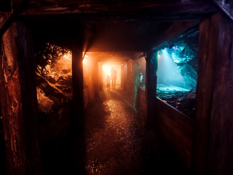 Two people walking in a dark abandoned mine.