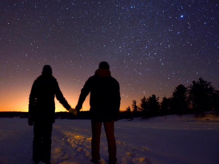 A couple holding hands while viewing the night sky in Muskoka.