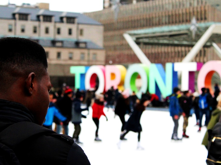 Man watching crowds of ice skaters at Nathan Phillips Square
